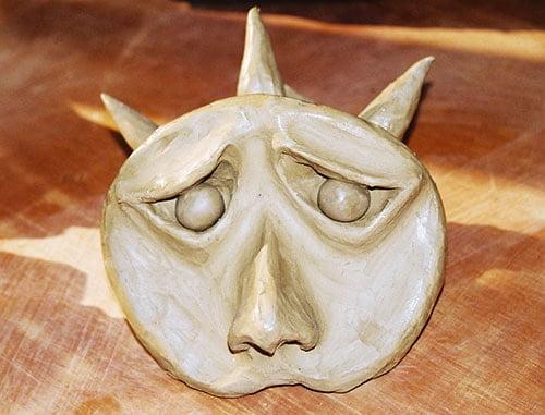 Rosto expressivo modelado em argila